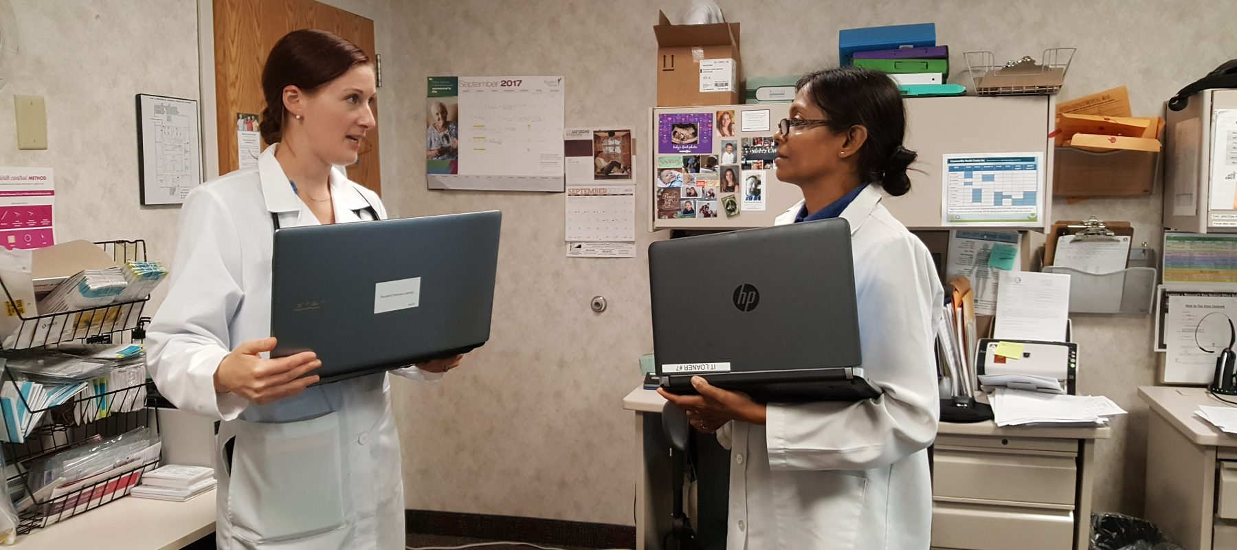 Two women in white coats talking to each other holding laptops in a doctors office