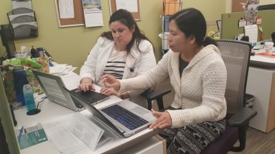 Two women sitting at desk working on laptops